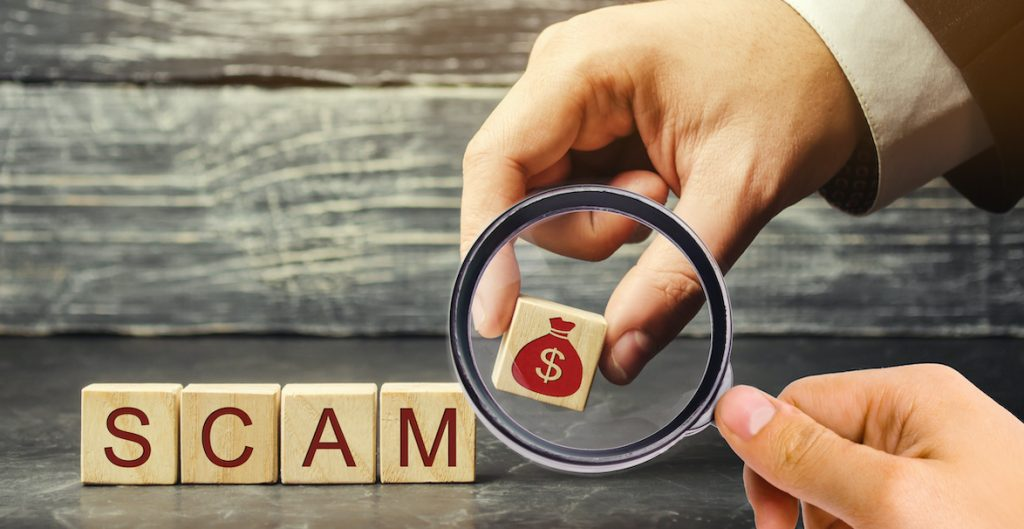 Businessman puts wooden blocks with the word Scam.